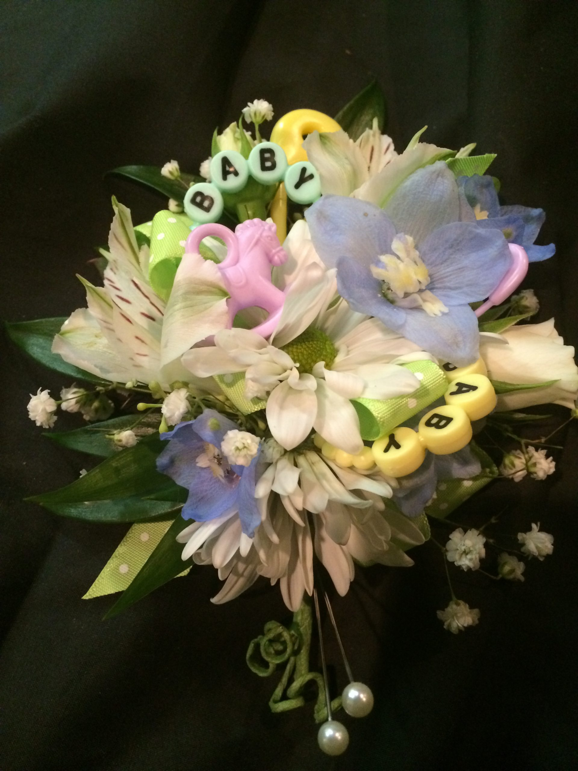 Baby shower corsage with baby toys in pastels