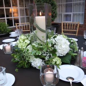 This bride and groom had a green and white wedding palette. In keeping with their wishes, we used Queen Anne's lace, white hydrangea, green hydrangea, green hypericum berries, bear grass, and a 16-inch square candle shade with a 12-inch pillar candle.