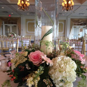 This bride and groom had a pink and white wedding palette. In keeping with their wishes, we used Queen Anne's lace, white hydrangea, pink gerber daisies, pink roses, pink hypericum berries,  white wax flower and pink yarrow. The flowers were complemented with a 16-inch square candle shade and a 12-inch pillar candle.